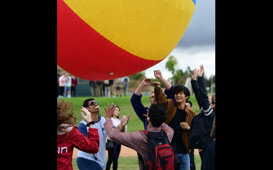 students paying with large beach ball